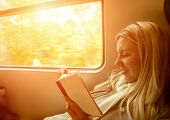 Happiness woman reading book in train under sunlight