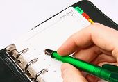 Hand With A Green Pen Writing In An Organizer