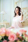 Beautiful Pregnant Girl In A Lace Negligee Sitting On A Bed Of Roses And Touching Hair
