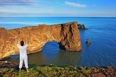 Cape Dirkholaey in the south of Iceland. The enthusiastic woman- tourist welcomes the rock - elephant