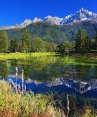 Snowy mountains and evergreen forests in the famous mountain resort of Chamonix. Gorgeous reflection