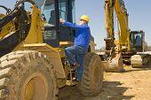 Construction Worker Climbing On Equipment