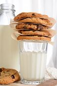 Closeup of a stack of fresh baked cookies on top of a glass of milk. Vertical format with a bottle of milk and flour in the background. Chocolate Chip, Oatmeal Raisin, White Chocolate cookies.