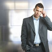 Young unsure caucasian businessman in suit standing and thinking in front of business office wall. Scratching head, wondering, hand in pocket. Copyspace, indoor.