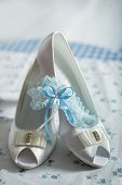 Bride shoes garter, with blue ribbon, and blue background. Closeup of wedding accessories.