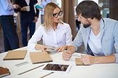 Male and female designers choosing color from palette in office