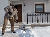 stock photo of snow shovel  - Man clearing path to his house of snow with shovel after heavy snowing - JPG