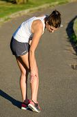 Female Athlete Suffering A Calf Muscle Cramp Injury While Running