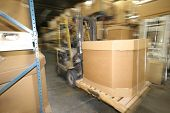 stock photo of prone  - busy lift truck driver moves inventory or box on a skid in a manufacturing plant - JPG