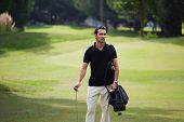 Attractive male golf player at the course with a club sack