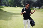 Professional golf player looking at the ball walking on course