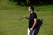 Confident male golfer holding driver and black golf bag