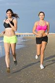 Two slender, fit women running along the shoreline during a workout and evening jog