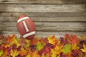 Football With Fall Leaves On Rough Wood Top View