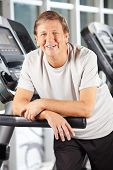 Active smiling senior man on treadmill in fitness center