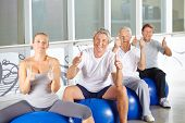 Happy group of senior people in fitness center holding thumbs up