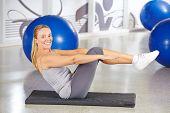 Sportive elderly woman doing gymnastics in a gym