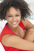 A beautiful mixed race African American girl or young woman wearing a red dress looking happy and sm