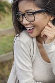 Portrait of a beautiful Chinese Asian girl or young woman outside wearing glasses happy and laughing