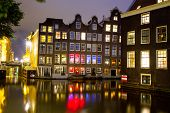 Historic buildings of old Amsterdam and canal at night.