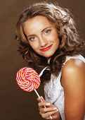 Lollipop in hand. Beautiful curly girl with  candy.