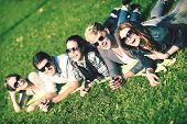 summer holidays, education, campus and teenage concept - group of students or teenagers hanging out