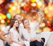 family, holidays, technology and people concept - smiling mother, father and little girl making self