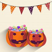 Pumpkin basket ful of lollipops and bunting on beige background for Halloween party celebration.