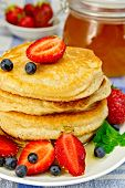 Flapjacks with strawberries and blueberries on linen tablecloth
