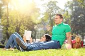 Boyfriend and girlfriend relaxing in park on a sunny day