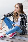 Young beautiful girl sitting on a pier, listening to music from her smartphone