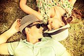 stock photo of sweet dreams  - Happy young couple relaxing on the lawn in a summer park - JPG