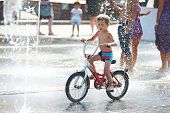 Little Boy Rides His Bike Among Fountains