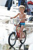 Little Boy Rides His Bike Among Puddles