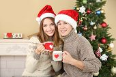 Nice love couple sitting with mugs in front of fireplace near Christmas tree. Woman and man celebrat