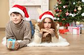 Young couple with gifts on carpet, at home