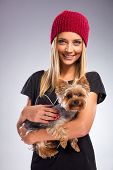 Beautiful woman with autumn fashion holding yorkshire terrier dog