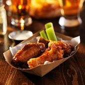 basket of barbecue buffalo chicken wings with celery sticks and ranch sauce