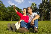 Asian Senior Couple Sitting On Grassland And  Taking Picture