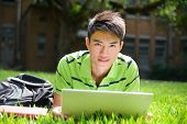 Young male college student lying on use laptop at campus