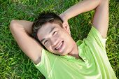 Portrait of Asian student lying on on the green grass