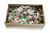 Many Puzzle Pieces In A Cardboard Box