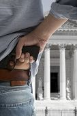 Security man holding gun against an courthouse background