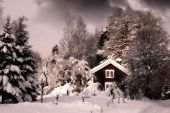 small red cottage surrounded by snowy winter landscape, at dusk, typica scenery from Sweden
