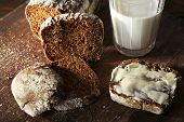 Sliced rye bread and glass of fresh milk on cutting board on wooden background