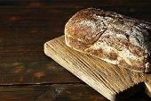 Rye bread on cutting board on wooden background