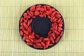 Goji berries in black saucer on bamboo mat background