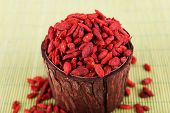 Goji berries in wooden bowl on bamboo mat background