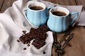 Cups of coffee with chocolate and napkin on wooden table