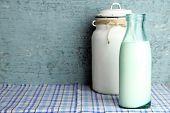 Retro still life with tasty rustic milk, on table